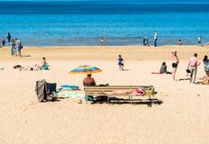 People enjoy the sunny spring day on the Baltic sea gulf beach in the Maiori resort, Jurmala. Royalty Free Stock Photo
