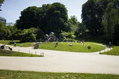 People enjoy sunny weather and children play. At a playground at park Parc des Buttes-Chaumont in Paris. It is a spring day stock photography