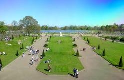 People enjoy sunny weather at Kensington Palace garden stock photos