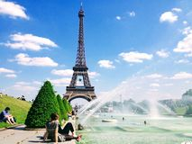 People enjoy sunshine and fountain pool in front of the Eiffel Tower. Paris, France stock images