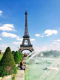 People enjoy sunshine and fountain pool in front of the Eiffel Tower royalty free stock image