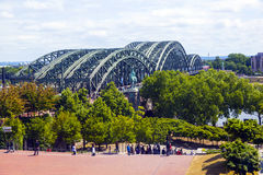 People enjoy to walk along the promenade at the Hohenzollern bridge Royalty Free Stock Images