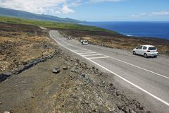 People enjoy the view to the asphalt road over volcanic lava in Sainte-Rose De La Reunion, France. royalty free stock photo