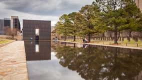 People Enjoy Visiting OKC Bombing Memorial. OKLAHOMA CITY, OKLAHOMA / USA - MARCH 31, 2018: People walking around and visiting the OKC Bombing Memorial and Royalty Free Stock Images