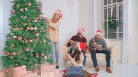 People enjoy winter holiday. Decorating christmas tree. Happy friends enjoy free time new year eve. Young family preparing for a party. Caucasian blonde women stock photos