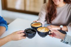 Free People Enjoyed Drinking And Clinking Coffee Cups Together On The Table In Cafe Royalty Free Stock Photo - 164785795