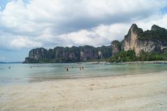 People enjoying the blue sky and the turquoise beach with rocks in Krabi, Thailand royalty free stock photo