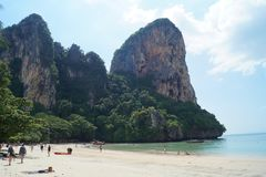 People enjoying the blue sky and the turquoise beach and rocks in Krabi, Thailand royalty free stock photo