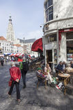 People enjoying a drink on the market near breda cathedral Stock Image