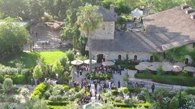 People enjoying drink and wedding event in the green garden surrounded by vineyard.