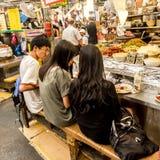 People enjoying fast food at Gwangjang Market. One of the most popular street food place where you can buy kimbap, teokbokki, stock photo