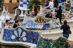 People enjoying mosaic tile benches in Parc Guell. BARCELONA, SPAIN - APRIL 22, 2010:  People enjoying art nouveau mosaic tile benches designed by Antonio Gaudi Royalty Free Stock Photos