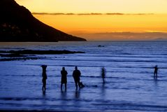 People enjoying the ocean. People standing in the ocean after sunset in Gordon's Bay, South Africa. Slow shutter speed results in some movement on people and the stock images
