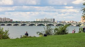 People enjoying the outdoors on Belle Isle with the iconic MacArthur Bridge in the background. Royalty Free Stock Photo