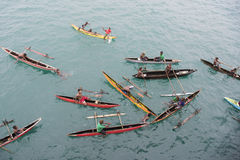 People enjoying rain in canoes on Pacific Ocean
