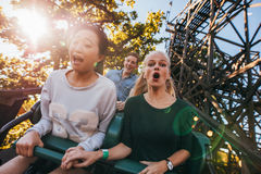 People enjoying a ride in amusement park. Shot of young friends enjoying riding roller coaster at amusement park. Young people having fun on rollercoaster Stock Photo