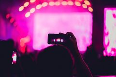 People enjoying rock concert and taking photos with cell phone a royalty free stock image