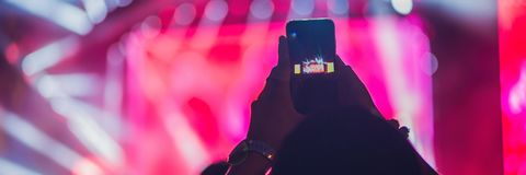 People enjoying rock concert and taking photos with cell phone at music festival BANNER, long format stock photo