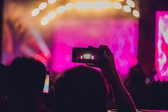 People enjoying rock concert and taking photos with cell phone at music festival stock photography