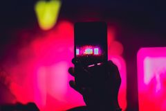 People enjoying rock concert and taking photos with cell phone a royalty free stock images