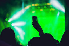 People enjoying rock concert and taking photos with cell phone a stock photos