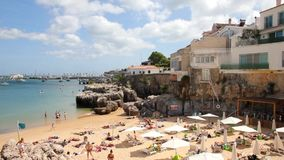 People enjoying the summer day in the beach Praia da Rainha, Cascais, Portugal stock footage