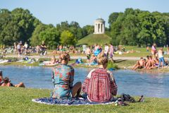 People tanning, swimming and enjoying the summer in Englischer Garten in Munich, Germany. Royalty Free Stock Photography