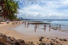 People enjoying the summertime on Rainbow Bay beach. stock image