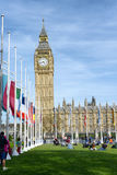 People enjoying the sun in front of Big Ben. And the Houses of Parliament, Westminster, London, UK, relaxing on the green lawns alongside the row of Royalty Free Stock Photo
