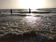 People Enjoying the Sun Set With The Sea Water. royalty free stock photos
