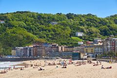 People enjoying a sunbathing in Zurriola beach of San Sebastian. Royalty Free Stock Images