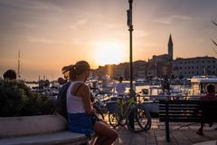 People enjoying the sunset in front of the old town of Rovinj in Croatia. Wonderful sunset in the awesome little town rovinj in istria - croatia. Golden hour is Stock Photography