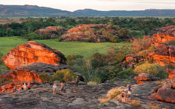 People enjoying the sunset light at Ubirr Rock, Australia. Ubirr Rock, Australia -May 29, 2016: The reflected sunset light on the rocks to the sacred site at Stock Image