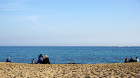 People enjoying sunshine during cold weather at barceloneta beach Stock Images