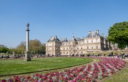 People enjoying sunshine in the Luxembourg garden - Paris. Paris, France - April 11, 2019: People enjoying sunshine in the Luxembourg garden with the Senat in stock photos