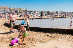 People enjoying the Swimming Pool on the Beach. Weston-super-Mare, United Kingdom -  June 17, 2017: People are enjoying the hot weather on the beach and are Stock Photo