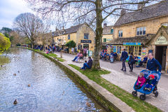 people enjoying their day along the water on a fine day at Bourton On the Water, England stock photography