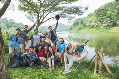 People enjoying their holiday camping together. Excited young people enjoying their holiday camping together by a lake Royalty Free Stock Photography