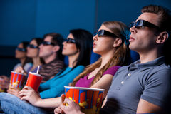 People enjoying three-dimensional movie. Young people in three-dimensional glasses watching movie while sitting at the cinema Royalty Free Stock Photos