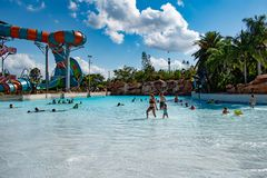 People enjoying wave pool and partial view of Karekare curl on lightblue sky cloudy background at Aquatica 1 stock photo