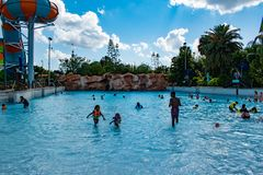 People enjoying wave pool and partial view of Karekare curl on lightblue sky cloudy background at Aquatica 4 royalty free stock photos