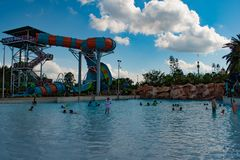 People enjoying wave pool and partial view of Karekare curl on lightblue sky cloudy background at Aquatica 3 royalty free stock images