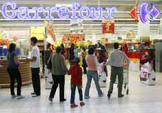 People entering Carrefour. People are passing by security system, entering the Carrefour supermarket