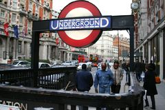 People entering the a London Underground station. London Tube logo at the entrance of one of the underground stations in London. The Tube`s logo, the roundel, a Stock Photography