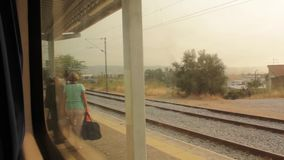 People entering train. Window view stock footage