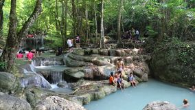 People in Erawan National Park and Erawan Waterfall in western Thailand stock footage