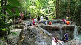 People in Erawan National Park and Erawan Waterfall in western Thailand. THAILAND, KANCHANABURI PROVINCE, APRIL 5, 2014: People in Erawan National Park and stock footage
