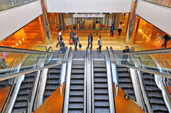 People on escalators in a shopping mall Stock Image
