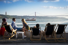 People in a esplanade in Lisbon, Portugal, by the Tagus River Stock Images
