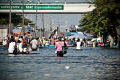 People evacuate from the flood. BANGKOK - NOVEMBER 13: A group of people evacuates from the flooded area at Sapan Mai district during the massive flood crisis on stock image
